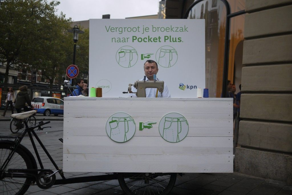 krawiec na ulicy powiększa kieszenia na sartfona
